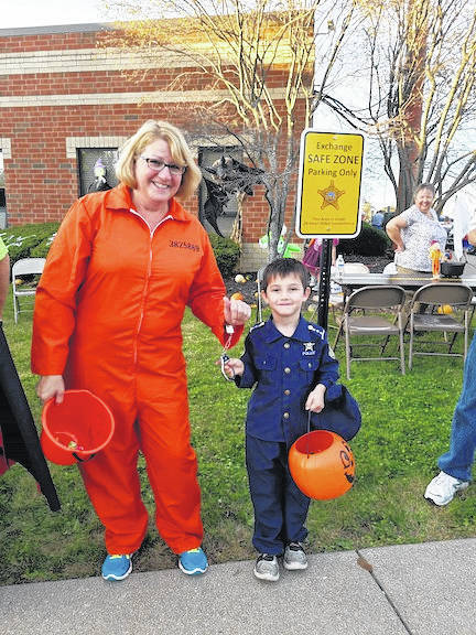 Janeen Wert from Job & Family Services dressed as a prisoner with a small law enforcement officer during Halloweenie event. The children lined up around the Morrow County Sheriff's Office and candy was passed out to them as they walked around the building. For many of the children this was their first time trick or treating. More photos online at morrowcountysentinel.com.