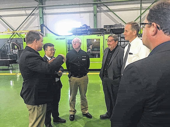 John Beary, president of Yizumi HPM, and James Zhang, general manager of Yizumi IMM division, and William Flickinger talk to Morrow County officials on Oct. 18 at an open house of the manufacturer's plant and office complex in Iberia.