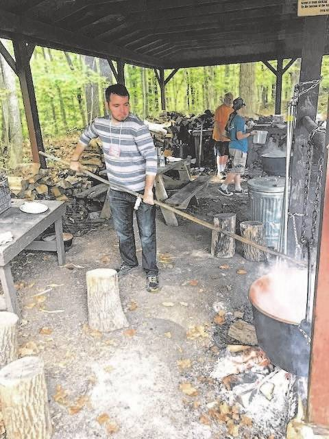 Volunteer John Buechele stirs apple butter as it cooks over the fire at the LMC Apple Butter Festival.