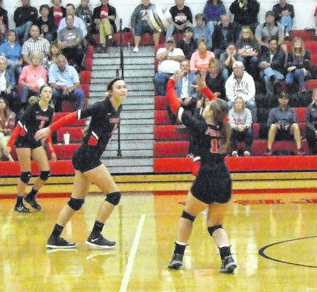 Cardington's Kyleigh Bonnette sets the ball, while teammates Casey Bertke (m) and Paige Clinger get into position.