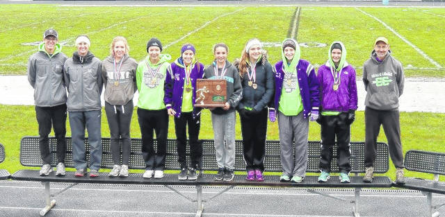 The Mount Gilead girls' cross country team poses with their Division III regional championship award after dominating the field at Pickerington on Saturday.