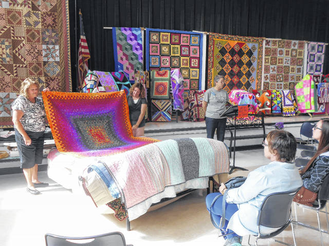 "Quilters, from left, Cheryl Jason, Kristin Crump and Kim Porter who participated in a ""Bed Turning."" Each member of the guild brought a quilt with a special story. This 1,000-piece quilt was made by Judy Rollenhagen."
