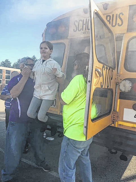 A student is helped down from the rear exit during Smoking A Bus program.