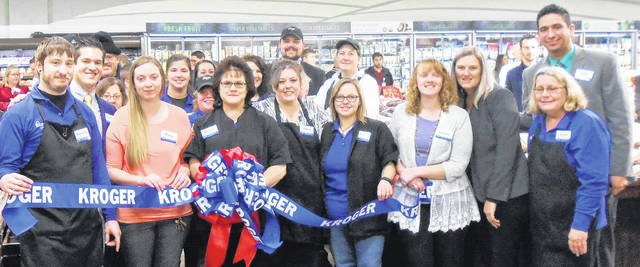 Kroger associates prepare to cut the ribbon at the Wednesday open house, celebrating the remodeling of the store.