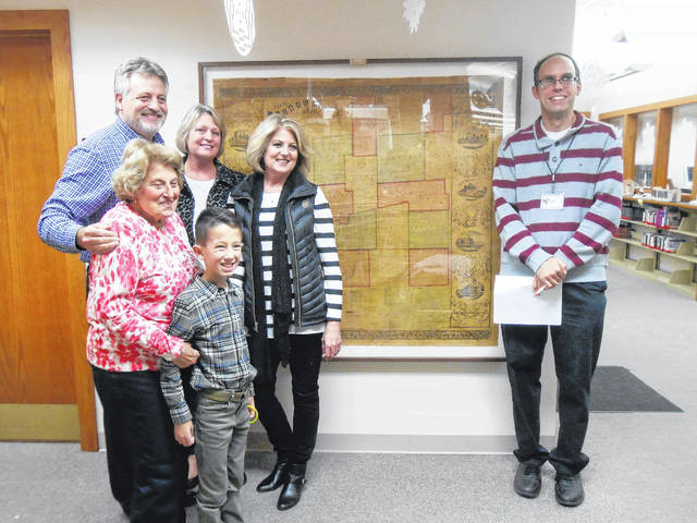 The Irons family with the 1857 map of Morrow County they donated to the Mount Gilead Public Library. Front, from left, are Pat Irons with Evan and, in back, Brad, Pam and Lindy Irons with Library Director Mike Kirk.