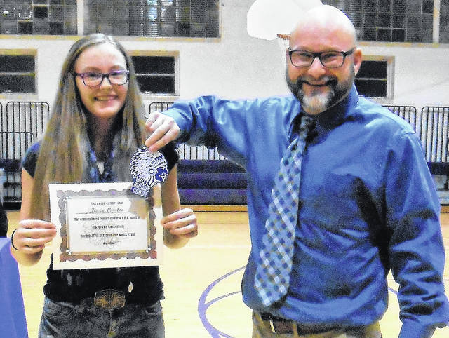 Mount Gilead Middle School Principa Jon Grega presents the Indian Pride award to eighth grader Jersie Preston at the Tuesday school board meeting.
