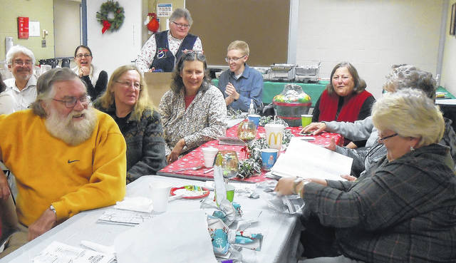 Debbie Tudor opens a mystery gift that turned out to be a Hillary mask. Morrow County Democrats held a mystery auction that raised $1,329 for food pantries in Morrow County.