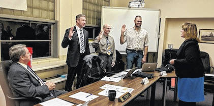 New Mount Gilead School Board members being sworn in by Municipal Court Judge Jenifer Burnaugh. From left are Mount Gilead School Superintendent Jeff Thompson, Matthew Griffith, Dennis West and Michael Sayers.