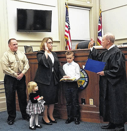 Jenifer Murphy Burnaugh receives her induction as Morrow County Municipal Court Judge Tuesday afternoon from Judge Robert C. Hickson Jr. Holding the Holy Bible is Joshua Burnaugh accompanied by Addison Burnaugh. More photos at morrowcountysentinel.com.