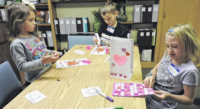 Belle and Zeke Kincaid and Grace Ernsberger make Valentine's Day crafts at Selover Public Library's Homeschool Book Club.