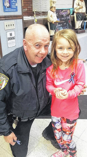 Northmor second grader Ryliee Hobson is pictured with Capt. Kenny Underwood of the Mount Giliead Police Department.  Hobson has been making ribbons and donating all proceeds to support the Westerville Police Department.