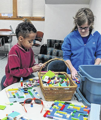 Cody Kipp and Tommy Emberg are focused on building a marble maze with Lego blocks at the Mount Gilead Public Library Lego Club. The group meets on the third floor of the library.