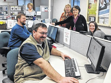 The Ohio Means Jobs team is seated at the bank of computers that are available for clients to use when they come in to research available employment or find information about a career or work. In front on the left is Joe Byrne and Eric Uhde. Jennifer Kennon is in back and on the right are Teresa Shipman, Nan Crothers and Tara Lawyer.