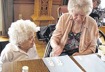 Morrow Manor residents Pauline and Marilyn work on their snowman crafts.