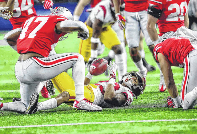 Ohio State linebacker Justin Hilliard (left) celebrates along with Ohio Statewide receiver Austin Mack as they make a big tackle on the kickoff return of USC's Velus Jones Jr. during the 82nd Goodyear Cotton Bowl Classic at AT&T Stadium Dec. 29, 2017.