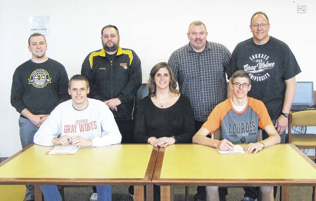 As they both sign to play basketball for Lourdes University, Tyler (left) and Kyle Kegley sit in the front row with their mother, Heidi. In the back row are Northmor basketball coaches Blade Tackett, Zach Ruth and Ben Pletcher, as well as their father, Jack.