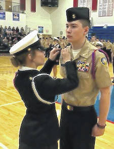 Outgoing Company Commander Melissa Bonner pins the rank device on incoming Company Commander Trea Renwick.