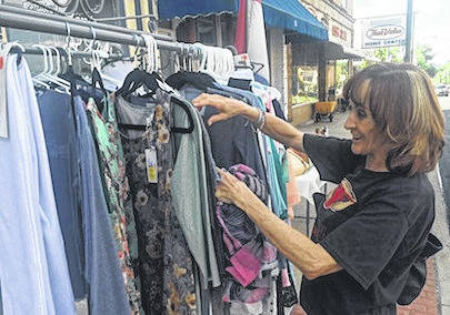 Lori Treisch of Mount Gilead shops for bargains at Gardens & Gifts Friday during the annual downtown Sidewalk Sales.