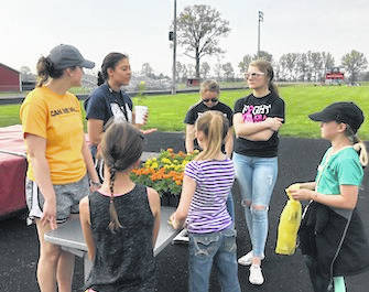 Makenna McClure and Olivia Jones teaching third graders about flowers during the Food for America program.