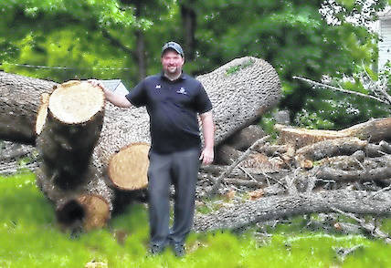 Jamie Brucker with the trunk of the old ash tree that was felled on his property this week. The tree is estimated to be from 150 to 200 years old.