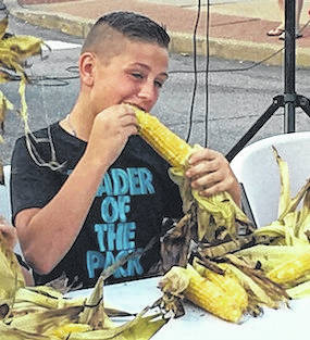 Young and old alike enjoy sweet corn during last year's festival in downtown Mount Gilead. A total of 208 dozen ears were consumed.