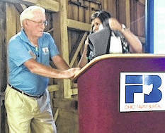 Don Bloom receives an award from Heather Goodman, president of the Morrow County Farm Bureau for his work in organizing this meeting.