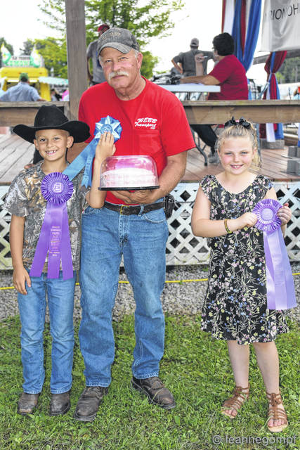 Winners of the Children's Cake baking contest at the Morrow County Fair left is Robby Schmidt, grand champion children's cake winner with a representative from Webb Transport who purchased the cake for $200. On the right is Natori Clevenger, who baked the reserve champion cake. It was purchased by Sanders for $225 who was not present for photo.